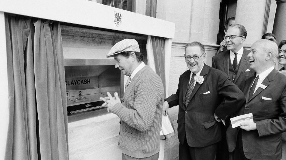 Bange Erwartung: Schauspieler Reg Varney hebt im Juni 1967 als erster Mensch Geld mittels Automat ab. Die damalige Chefetage der Barclays Bank freut's.
