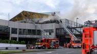 16.05.2019: Feuerwehrleute löschen von Drehleitern aus ein Feuer, das in der Mainzer Rheingoldhalle ausgebrochen war.