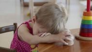 Ein Mädchen legt seinen Kopf auf den Tisch.