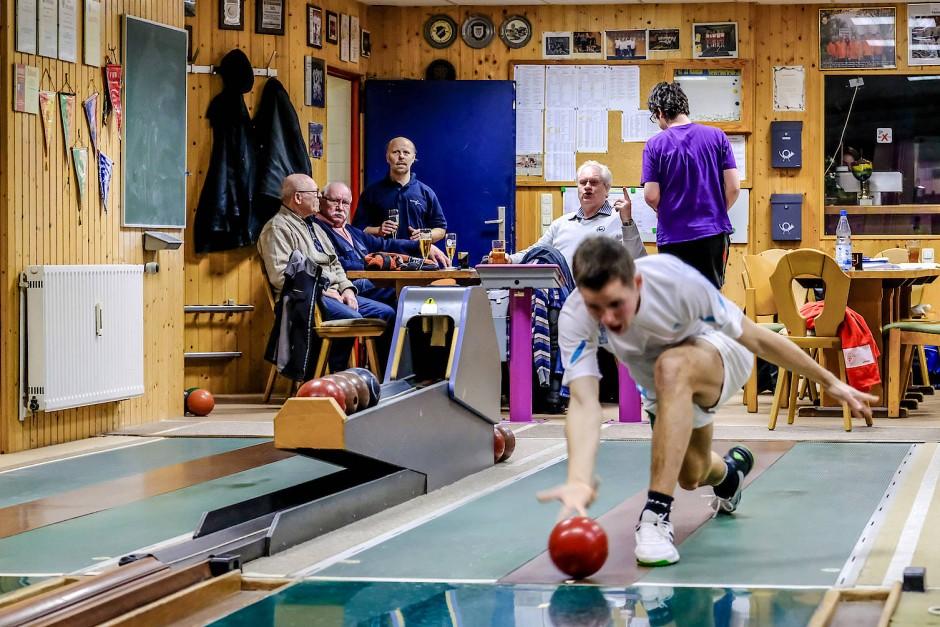 Niklas Albert lässt die Kugel rollen, die älteren Klubmitglieder trinken Bier und schauen zu.