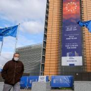 Ein Mann mit einer Schutzmaske geht in Brüssel am Sitz des Europäischen Rats vorbei.