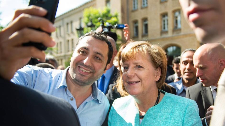 Ein täuschendes Bild: Dass von den berühmten Selfies von Flüchtlingen mit der Bundeskanzlerin eine zusätzliche Anziehungswirkung auf Migranten ausgegangen sei, ziehen Kieler Wissenschaftler in Zweifel.