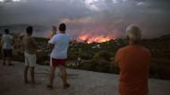 Das Feuer frisst sich bis zur Küste: Anwohner blicken am Montagabend auf die Brände in Rafina.