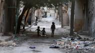 Kinder laufen am Freitag durch die zerstörten Straßen von Aleppo.