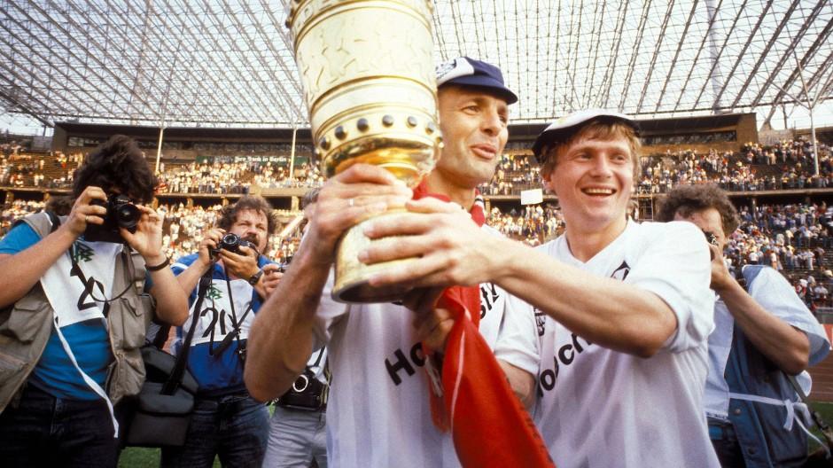Karl-Heinz Körbel (links) zusammen mit Lajos Detari (rechts) und dem DFB-Pokal