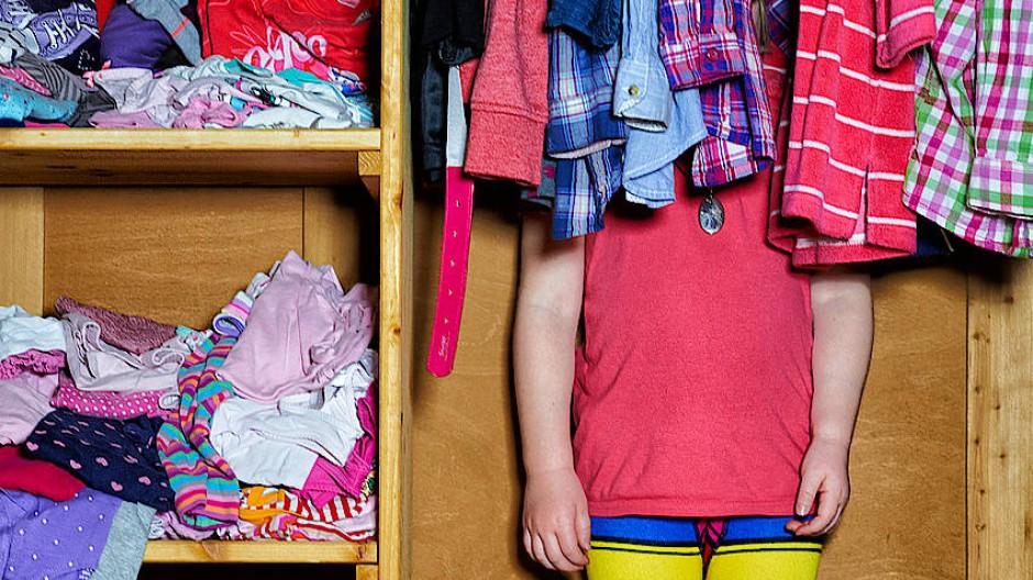 In dem Kleiderschrank des Mädchens ist noch so viel Platz, dass es sich darin verstecken kann.