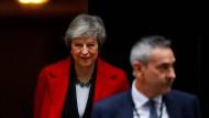 Theresa May ist tapfer am Lächeln, obwohl für Sie der politische Überlebenskampf weitergeht.