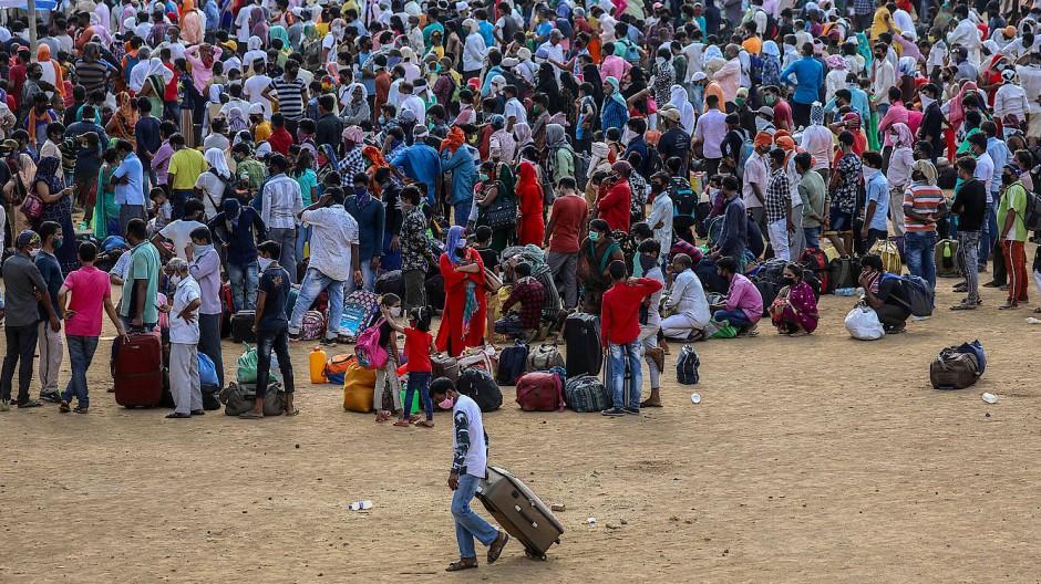 Wanderarbeiter stehen dicht gedrängt in Mumbai, um in Busse zu gelangen.