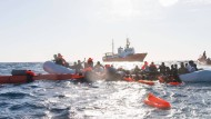 Flüchtlinge, die auf Booten von Libyen aus nach Italien übersetzen wollten, werden während eines Rettungseinsatzes im Mittelmeer geborgen.