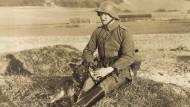 Ein Deutscher Soldat mit Stahlhelm und einem Hund.
