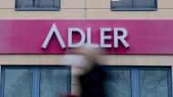 Eine Frau mit Mund-Nase-Bedeckung geht an einem Schild des Unternehmens «Adler Modemärkte» an einem Einkaufszentrum vorbei.