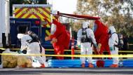 Mitarbeiter des FBI und des Gefahrgut-Dienstes reinigen ihre Schutzanzüge nach dem Einsatz bei Facebook in Kalifornien.