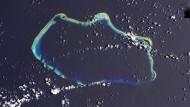 """Alles Korallen: Das Bikini-Atoll ragt nur an wenigen Stellen (dunkelgrün) aus dem Wasser. Links oben erkennt man den Krater der Wasserstoffbombe """"Castle Bravo""""."""