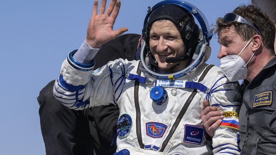 Der russische Kosmonauten Sergej Kud-Swertschkow (M) winkt kurz nach der Landung der russischen Raumkapsel Sojus MS-17.