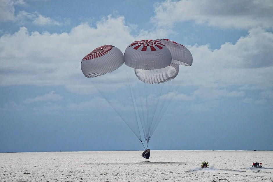 Die Dragon-Raumkapsel erreicht vor der Küste von Florida das Meer.