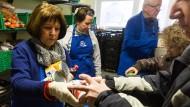 Helfer verteilen Lebensmittel in der Frankfurter Tafel.
