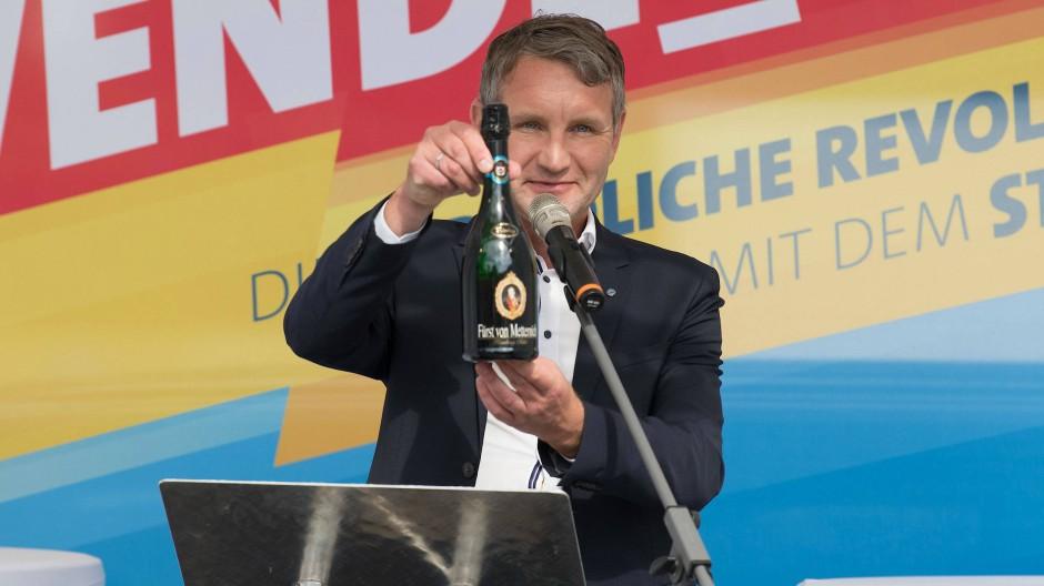 Mit einer Flasche Sekt verhöhnt Björn Höcke die wohl anwesenden Staatsschützer beim Wahlkampfauftakt der Brandenburger AfD in Cottbus.