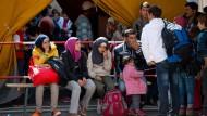 Allein an diesem Samstag sind rund 10.000 Flüchtlinge am Münchener Hauptbahnhof angekommen. Die Menschen auf dem Foto warten auf einen Bus, der sie in eine der Erstaufnahmeeinrichtungen fahren soll.