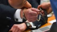 Dem Angeklagten im S&K-Betrugsprozess Jonas K. werden im Gerichtssaal des Landgerichts Frankfurt am Main am 24.09.2015 die Handschellen abgenommen.