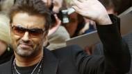 """George Michael winkt zum Abschied, als er bei der Berlinale 2005 die Pressekonferenz für seinen Film """"George Michael, A Different Story"""" verlässt."""