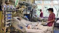 In einem Krankenhaus in Halle arbeiten Pfleger auf der Interdisziplinären Intensivstation mit Covid-19 Bereich am Bett eines Patienten von Patienten.
