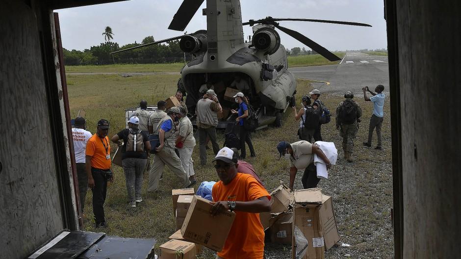 Menschen entladen humanitäre Hilfe aus einem Hubschrauber der US-Armee auf dem Flughafen in Les Cayes.