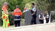 Polizisten und Rettungssanitäter stehen an der Einfahrt zum Wohnhaus, in dem der Familienvater seine Frau und einen Sohn getötet haben soll.