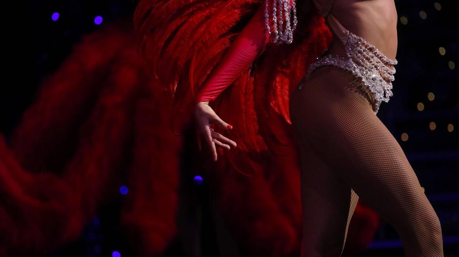 Eine Tänzerin präsentiert sich mit roten Federflügen während der  Wiederaufführung von Féerie im Moulin Rouge.