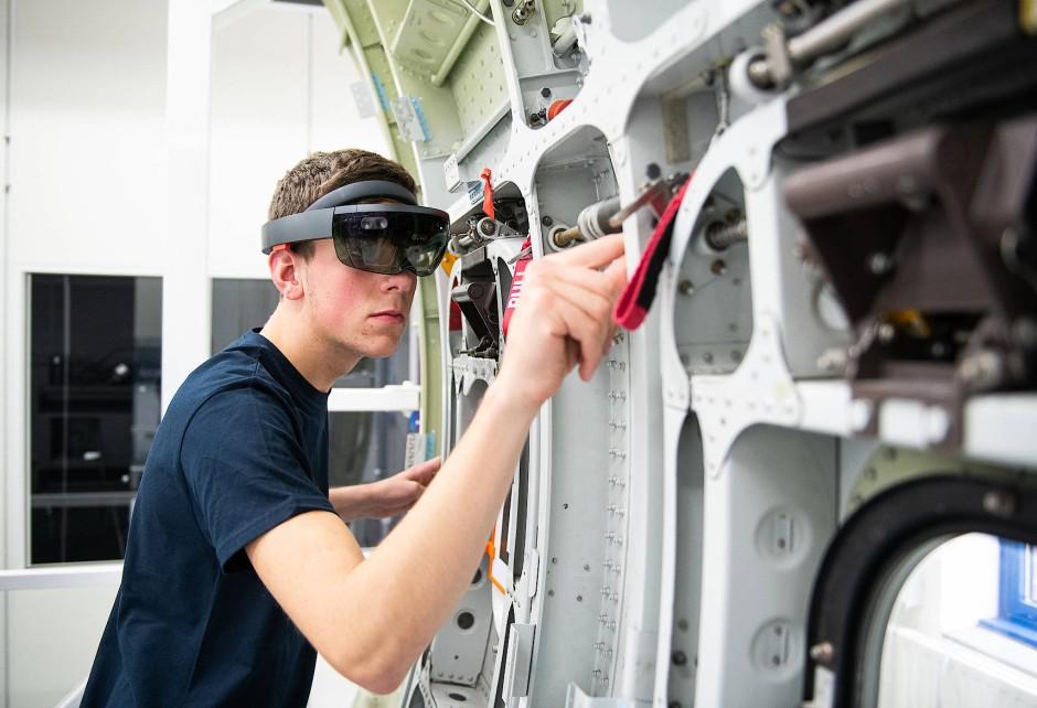 Virtuelle Hilfe: Ein Airbus-Auszubildender zeigt bei einer Demonstration den Einsatz einer Datenbrille (Microsoft Hololens) an einem Flugzeugbauteil.
