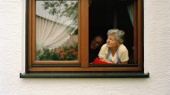 Ein altes Paar schaut aus dem Fenster.