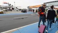 Mit Handgepäck: Passagiere in Berlin-Schönefeld auf dem Weg zum Flugzeug