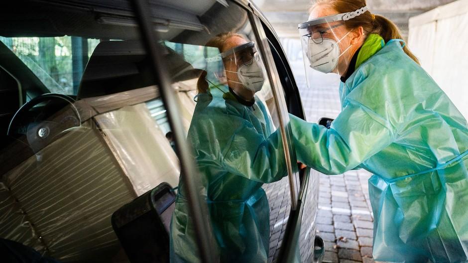 """Eine Helferin testet Insassen eines Autos im """"Testzentrum am Zoo"""" in Hannover mit einem Schnelltest auf das Coronavirus."""