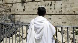 Stein aus Klagemauer verfehlt betende Frau
