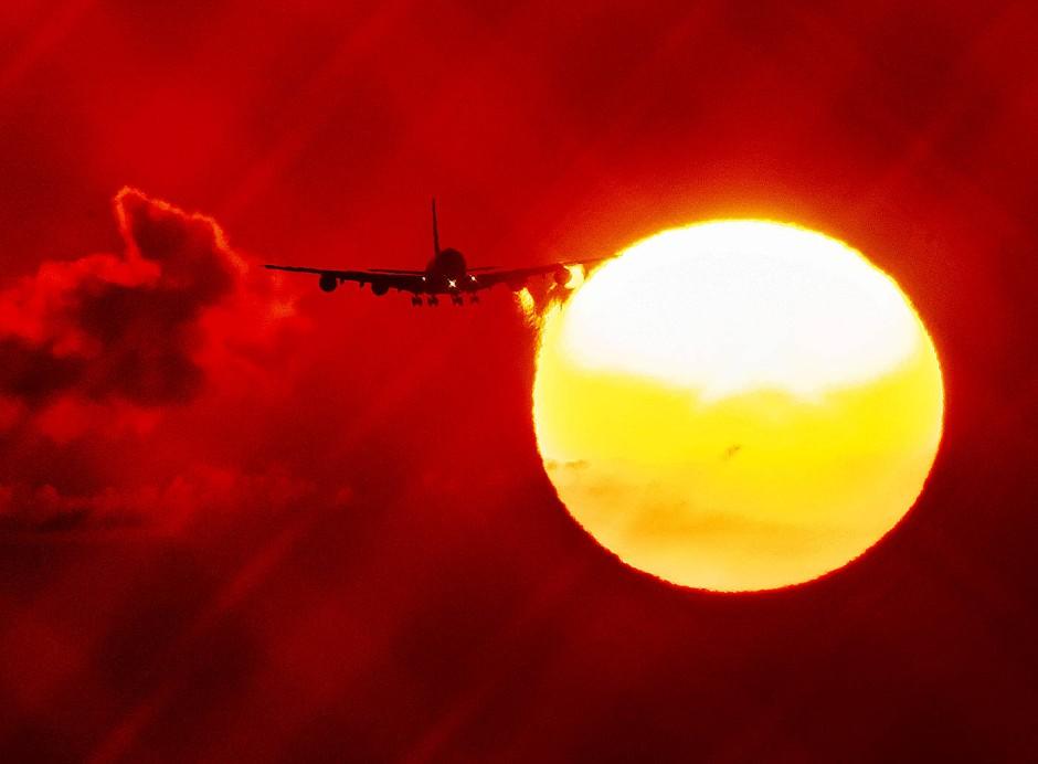 Ein Flugzeug passiert die aufgehende Sonne, als es sich dem Flughafen in Frankfurt nähert.