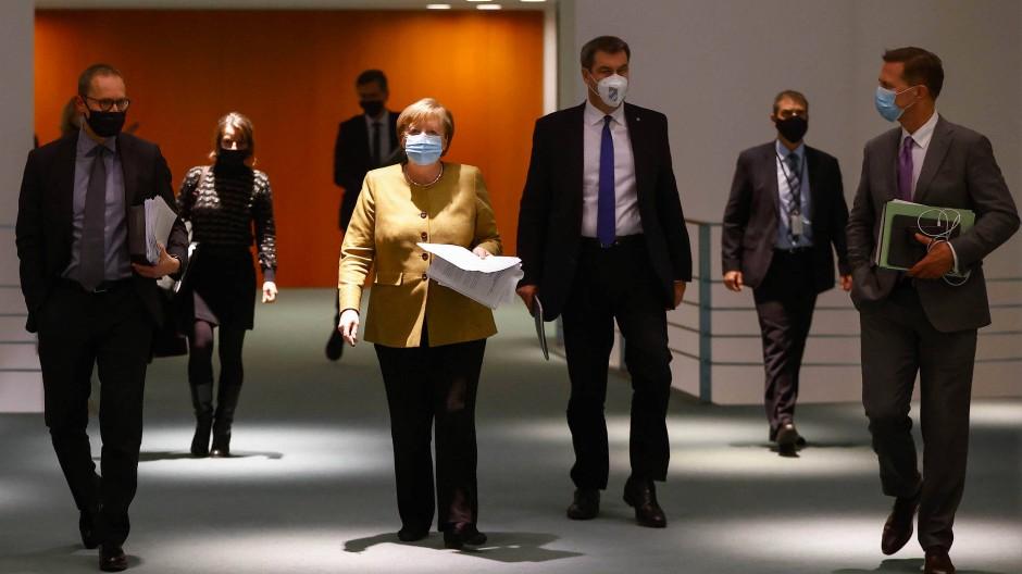Angela Merkel (Mitte), Berlins Regierender Bürgermeister Müller (l.) und Bayerns Ministerpräsident Söder auf dem Weg zur Pressekonferenz im Kanzleramt.