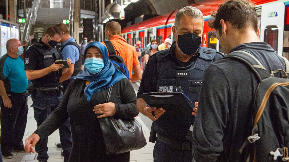 In Offenbach ist die Anzahl an Infektionen wieder stark angestiegen. Polizisten kontrollieren, ob Passanten in der S-Bahn den Mund-Nasen-Schutz tragen.