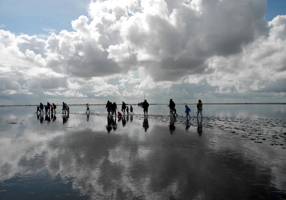 Wattwanderer am Strand von Juist. Heino, der Wattführer, ist eine unverwüstlichte Juister Gestalt.