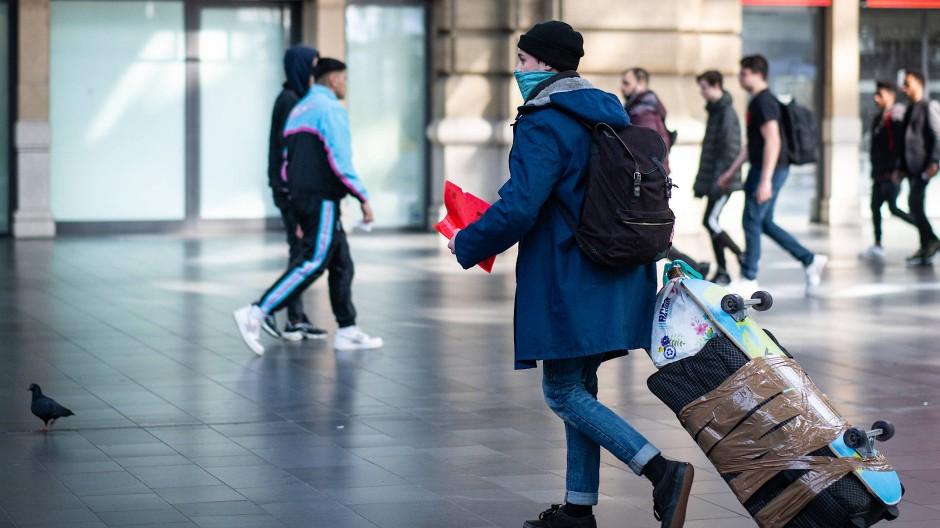 Ein Reisender mit Mundschutzmaske am Frankfurt Hauptbahnhof