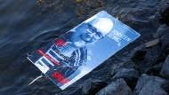 Ein Wahlplakat von Torsten Albig schwimmt in der Kieler Förde.
