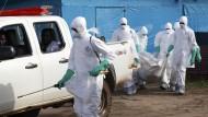 Medizinische Helfer in Schutzkleidung tragen den Leichnam einer mit dem Ebola-Virus infizierten Frau aus einer Quarantänestation in Liberia.