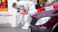Nach der Gewalttat: Ein Beamter der Spurensicherung legt am Dienstag Markierungstafeln auf den Asphalt.