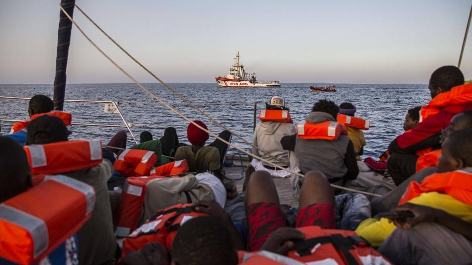 Migranten sitzen auf einem Boot einer Hilfsorganisation und steuern auf die italienische Insel Lampedusa zu.