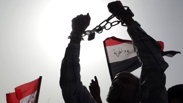 Protester, who opposes Egyptian President Mursi, holds up his hands, which are chained together, during a demonstration against Mursi and members of the Muslim Brotherhood in Cairo
