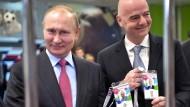 Der russische Präsident Wladimir Putin und Fifa-Präsident Gianni Infantino zeigen Anfang Mai beim Betreten des Olympiastadions ihre Akkreditierungen.