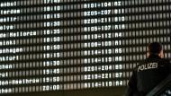 Erwartung: Ein Polizist steht vor einer Anzeigetafel im Flughafen Hannover