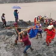 Mühsame Bergung: Die Verschütteten werden in Planen und an Bambusstangen weggetragen.