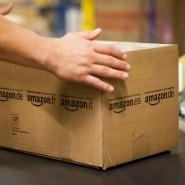 Ein Mitarbeiter von Amazon greift im Amazon Logistikzentrum nach einem Paket.