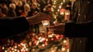 Gedenkveranstaltung in Berlin: Zwei Jahre nach dem Terroranschlag am Breitscheidplatz übergibt eine Frau nach einer Abendandacht ein Kerzenlicht.