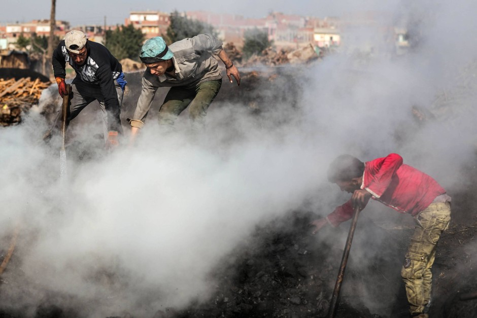 Rauch steigt aus einer Kohlegrube. Um die Kohle abkühlen zu lassen, verwenden die Köhler auch Wasser, das dann in dicken Dampfwolken zum Himmel steigt.