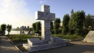 Am Ufer des aufgestauten Turja-Flusses erinnert ein Denkmal an die Toten der deutschen Arbeitsarmee, die das Aluminiumwerk im Hintergrund errichtete.